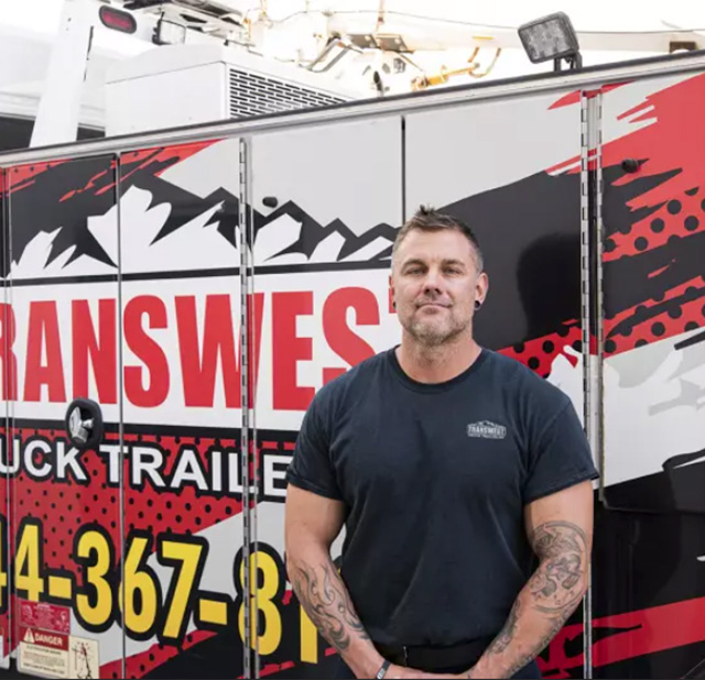 Diesel Technician standing in front of Transwest sign